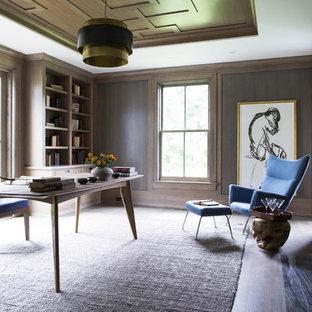 Bild på ett stort vintage hemmabibliotek, med bruna väggar, mörkt trägolv, en standard öppen spis, en spiselkrans i sten och ett fristående skrivbord