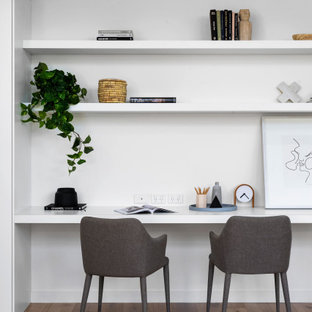 Mid-sized contemporary study room in Melbourne with white walls, a built-in desk, medium hardwood floors and beige floor.