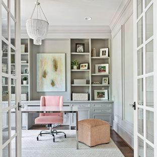 Inspiration för klassiska hemmabibliotek, med vita väggar, mörkt trägolv och ett fristående skrivbord