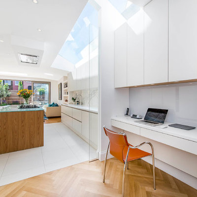 Inspiration for a small contemporary built-in desk light wood floor and beige floor study room remodel in London with white walls