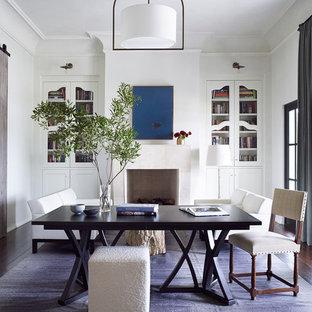 Immagine di un grande studio mediterraneo con libreria, pareti bianche, parquet scuro, camino classico, cornice del camino in pietra, scrivania autoportante e pavimento marrone