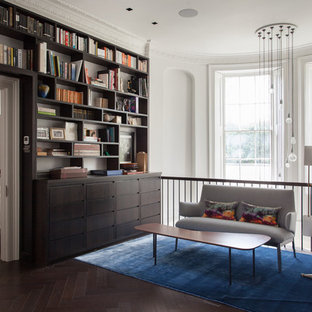 Design ideas for a traditional home office and library in London with a reading nook, white walls, dark hardwood flooring and brown floors.