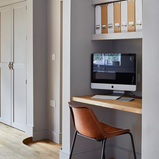 Design ideas for a small traditional study in Dorset with grey walls, light hardwood flooring, no fireplace and a built-in desk.