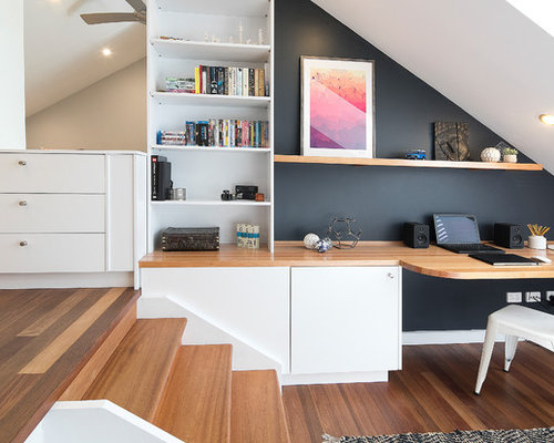 Inspiration for a modern home office in sydney with black walls laminate floors no