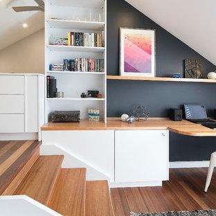 シドニーのコンテンポラリースタイルのおしゃれなホームオフィス・書斎 (黒い壁、ラミネートの床、暖炉なし、造り付け机、茶色い床) の写真