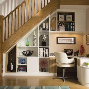 Klassisk inredning av ett litet hemmabibliotek, med vita väggar, mellanmörkt trägolv, ett inbyggt skrivbord och brunt golv