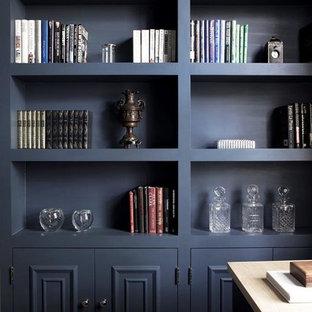 Mittelgroßes Klassisches Arbeitszimmer mit Arbeitsplatz, blauer Wandfarbe, braunem Holzboden, Kamin, Kaminsims aus Stein, freistehendem Schreibtisch und braunem Boden in London