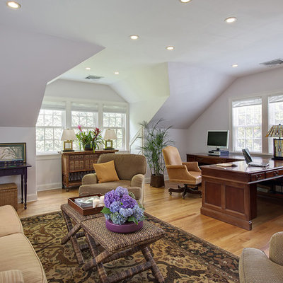 Large elegant built-in desk medium tone wood floor home office photo in New York with white walls