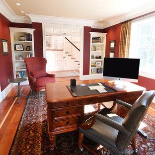 ボストンの中くらいのトラディショナルスタイルのおしゃれなホームオフィス・書斎 (赤い壁、無垢フローリング、暖炉なし、自立型机、茶色い床) の写真