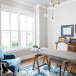 Foto di uno studio country con pareti grigie, pavimento in legno massello medio, scrivania autoportante e pavimento marrone