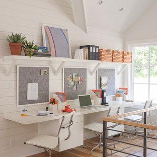 Inspiration för mellanstora klassiska hemmabibliotek, med vita väggar, ett inbyggt skrivbord och ljust trägolv