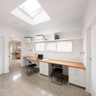Immagine di un piccolo studio design con libreria, pareti bianche, pavimento in cemento, scrivania incassata e pavimento grigio
