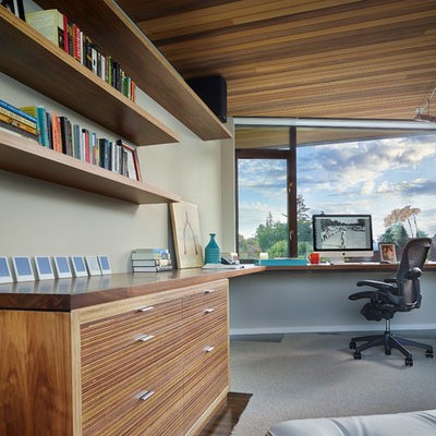 Example of a trendy built-in desk dark wood floor home office design in Seattle with gray walls