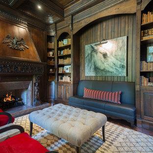 アトランタの広い地中海スタイルのおしゃれな書斎 (茶色い壁、自立型机、標準型暖炉、石材の暖炉まわり、濃色無垢フローリング) の写真