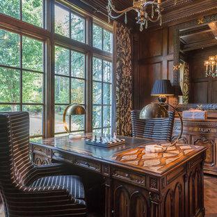 Großes Mediterranes Arbeitszimmer mit Arbeitsplatz, brauner Wandfarbe, braunem Holzboden, freistehendem Schreibtisch, Kamin und Kaminumrandung aus Stein in Atlanta