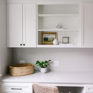 Réalisation d'un grand bureau craftsman avec un mur gris, un sol en bois clair, une cheminée double-face, un manteau de cheminée en carrelage, un bureau intégré, un sol marron et un plafond décaissé.