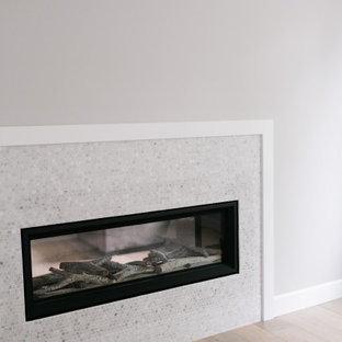 ポートランドの広いおしゃれな書斎 (グレーの壁、淡色無垢フローリング、両方向型暖炉、タイルの暖炉まわり、造り付け机、茶色い床、折り上げ天井) の写真