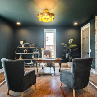 Klassisk inredning av ett arbetsrum, med gröna väggar, mellanmörkt trägolv, en standard öppen spis, en spiselkrans i tegelsten, ett fristående skrivbord och brunt golv
