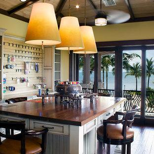 Exempel på ett exotiskt hobbyrum, med gula väggar, mörkt trägolv, ett fristående skrivbord och brunt golv