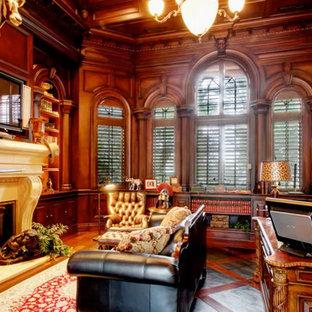 Idéer för stora tropiska hemmabibliotek, med bruna väggar, mörkt trägolv, en standard öppen spis, en spiselkrans i sten och ett fristående skrivbord