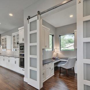 Study room - mid-sized modern built-in desk medium tone wood floor study room idea in Austin with gray walls