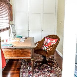 Ispirazione per un piccolo studio country con pareti gialle, pavimento in legno massello medio e scrivania autoportante