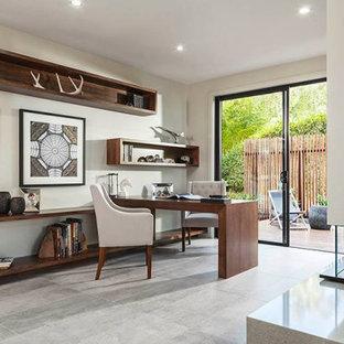 Idéer för att renovera ett stort funkis arbetsrum, med vita väggar, en dubbelsidig öppen spis, en spiselkrans i sten, ett inbyggt skrivbord och grått golv