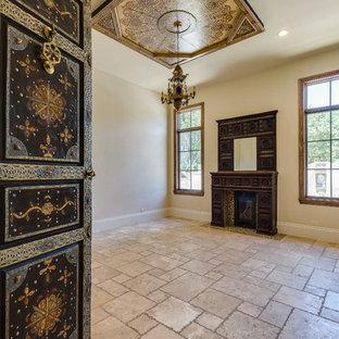 オースティンの広い地中海スタイルのおしゃれなホームオフィス・書斎 (ベージュの壁、トラバーチンの床、標準型暖炉、木材の暖炉まわり、ベージュの床) の写真