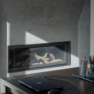 На фото: кабинет среднего размера в современном стиле с библиотекой, серыми стенами, паркетным полом среднего тона, двусторонним камином, фасадом камина из вагонки, отдельно стоящим рабочим столом и серым полом