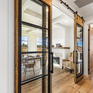Idéer för ett mellanstort lantligt hemmabibliotek, med vita väggar, mellanmörkt trägolv, en standard öppen spis, en spiselkrans i tegelsten, ett fristående skrivbord och brunt golv