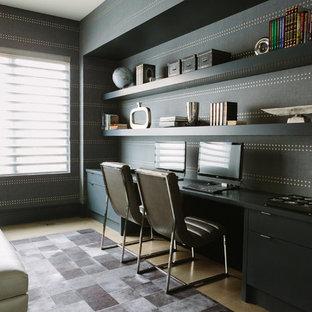 Idée de décoration pour un grand bureau minimaliste avec un mur multicolore, un sol en bois brun, un bureau intégré et un sol marron.