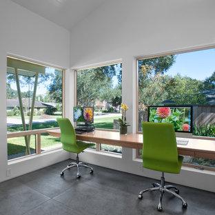 Modelo de despacho vintage con paredes blancas, suelo de baldosas de porcelana, escritorio empotrado y suelo gris
