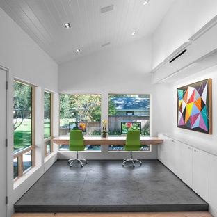 ヒューストンのミッドセンチュリースタイルのおしゃれなホームオフィス・書斎 (白い壁、磁器タイルの床、造り付け机、グレーの床) の写真