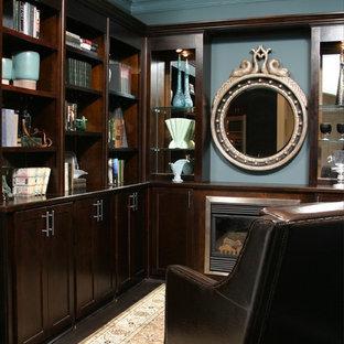 アトランタの小さいトラディショナルスタイルのおしゃれなホームオフィス・書斎 (ライブラリー、青い壁、濃色無垢フローリング、標準型暖炉、木材の暖炉まわり、造り付け机、黒い床) の写真
