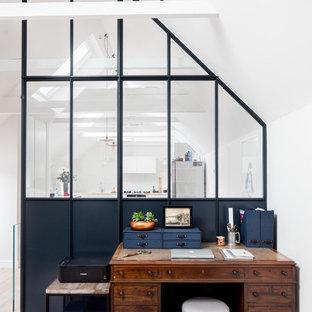 Idéer för att renovera ett litet eklektiskt hemmabibliotek, med ljust trägolv, ett fristående skrivbord, beiget golv och vita väggar