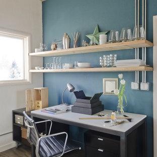 Idee per uno studio minimal con pareti blu, pavimento in compensato e scrivania autoportante