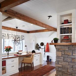 ミネアポリスの広いトラディショナルスタイルのおしゃれな書斎 (白い壁、濃色無垢フローリング、標準型暖炉、造り付け机、石材の暖炉まわり、茶色い床) の写真