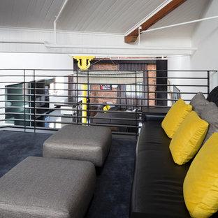 Cette image montre un grand bureau urbain de type studio avec un mur blanc, moquette, aucune cheminée et un sol bleu.