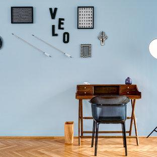 Mittelgroßes Modernes Arbeitszimmer ohne Kamin mit Arbeitsplatz, blauer Wandfarbe, braunem Holzboden, freistehendem Schreibtisch und beigem Boden in Berlin