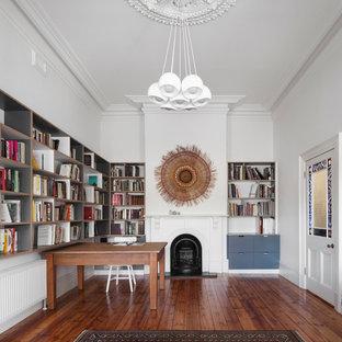 Inspiration pour un bureau nordique de taille moyenne avec une cheminée standard, un manteau de cheminée en bois, un bureau indépendant, un mur blanc et un sol en bois foncé.