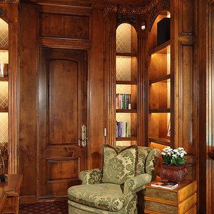 Klassisk inredning av ett stort hemmabibliotek, med bruna väggar, heltäckningsmatta, ett fristående skrivbord och rött golv