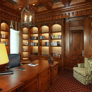 Diseño de despacho clásico, grande, sin chimenea, con paredes marrones, moqueta, escritorio independiente y suelo rojo