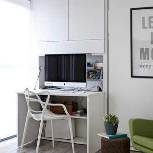 Inspiration for a contemporary built-in desk light wood floor study room remodel in London with white walls