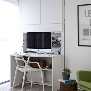 Imagen de despacho contemporáneo con paredes blancas, escritorio empotrado y suelo de madera clara