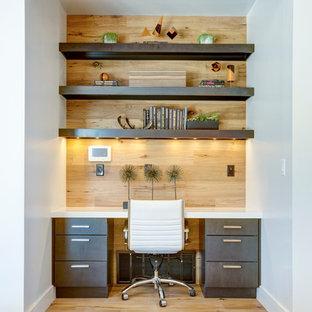 Modelo de despacho actual, pequeño, con suelo de madera en tonos medios, escritorio empotrado y paredes blancas