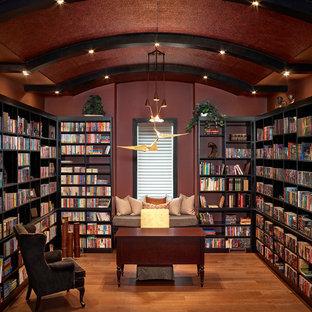 エドモントンの広いトランジショナルスタイルのおしゃれなホームオフィス・書斎 (ライブラリー、赤い壁、暖炉なし、無垢フローリング、自立型机、オレンジの床) の写真