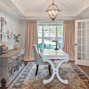 Cette image montre un grand bureau traditionnel avec un mur gris, un sol en bois foncé, aucune cheminée, un bureau indépendant, un sol marron et un plafond décaissé.