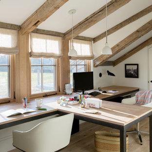 Пример оригинального дизайна: большое рабочее место в стиле кантри с белыми стенами, светлым паркетным полом, встроенным рабочим столом и коричневым полом