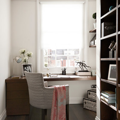 Trendy built-in desk dark wood floor home office photo in London with white walls