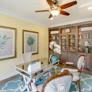 Idéer för mellanstora tropiska hemmabibliotek, med gula väggar, ett fristående skrivbord, mellanmörkt trägolv och brunt golv
